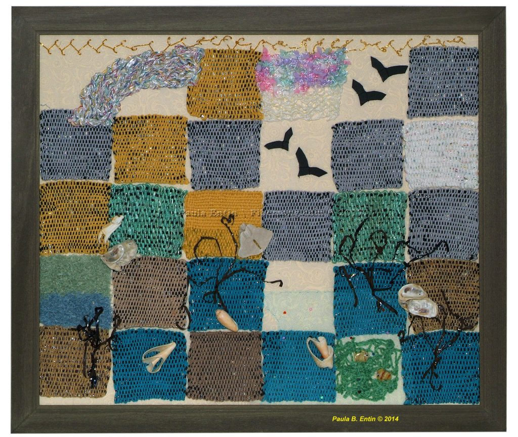 """Evocative of the restless seashore, this embellished creation consists of blocks woven with folk music cassette tape and exotic yarns, with added glass fish and various found objects.   Framed; 27"""" wide x 23"""" long."""